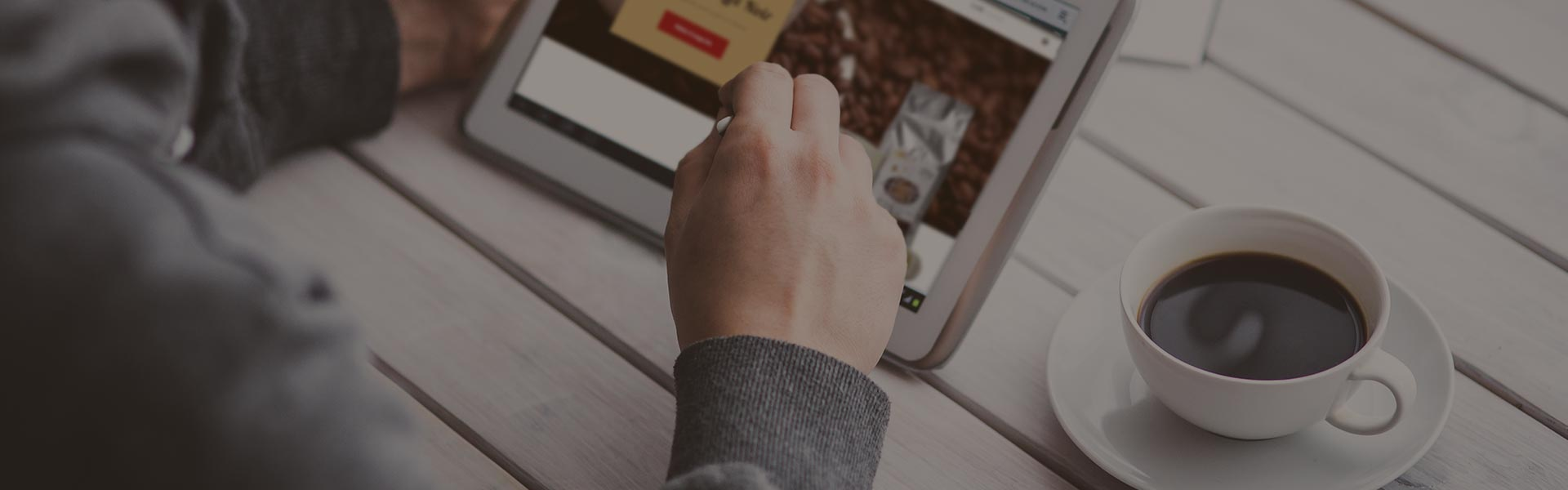 uomo che usa un tablet vicino a una tazza di caffè